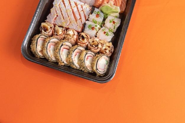 Sushi delicioso e bonito na mesa laranja Foto gratuita