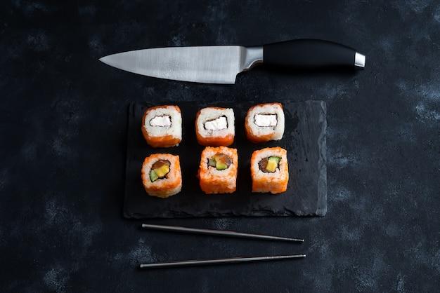 Sushi diferente, servido em uma placa de ardósia preta com faca japonesa e pauzinhos de metal Foto Premium