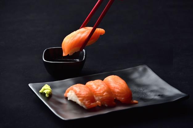 Sushi do nigiri e molho salmon do wasabi com os chopsticks no valvet preto. Foto Premium