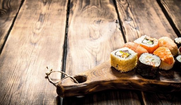 Sushi e pãezinhos no tabuleiro. em fundo de madeira. Foto Premium