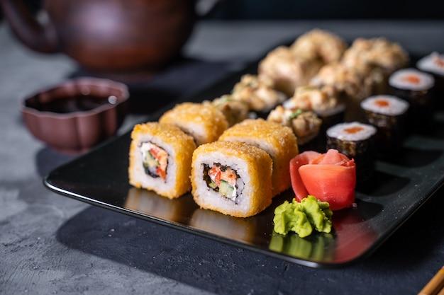 Sushi e sushi roll conjunto na vista superior de mesa de pedra preta Foto Premium