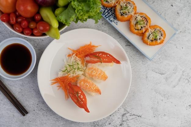 Sushi é um prato com pauzinhos e molho sobre um piso de cimento branco. Foto gratuita