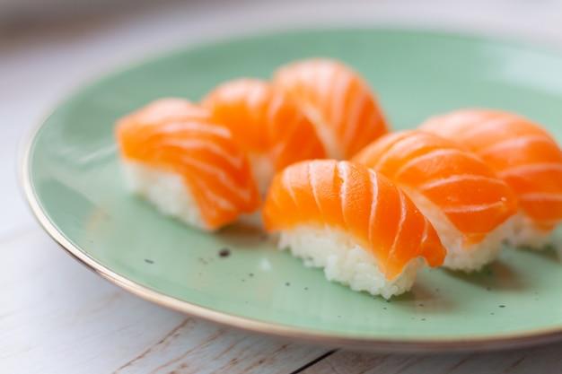 Sushi em prato de cerâmica, arroz e salmão Foto gratuita