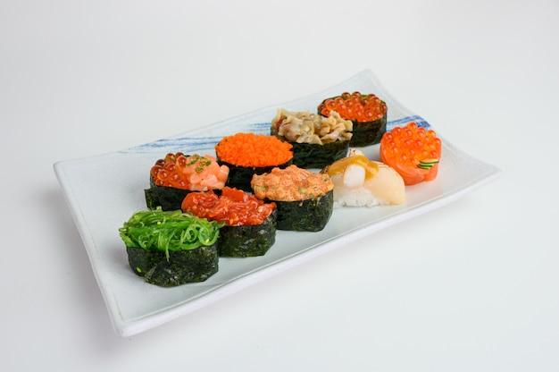 Sushi japonês de rolo de algas com ikura, ebiko, hotate, wakame, kurage na placa cerâmica Foto Premium