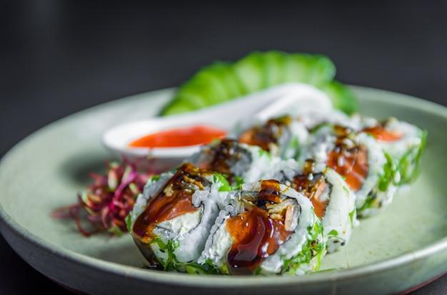 Sushi perfeito, cozinha tradicional japonesa. delicioso uramaki com molho agridoce no prato decorado, fundo preto. Foto Premium