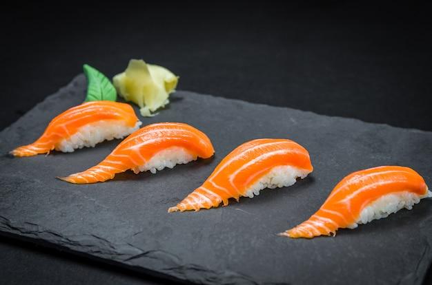 Sushi perfeito, cozinha tradicional japonesa. kiguiri de salmão delicioso no prato decorado, fundo preto. Foto Premium