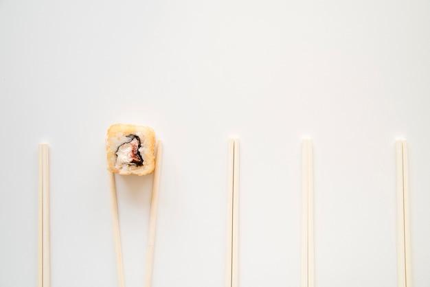 Sushi roll entre pauzinhos com cópia-espaço Foto gratuita