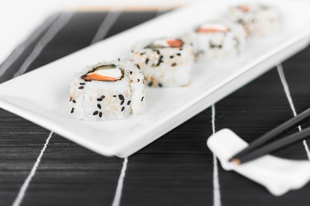 Sushi roll na bandeja branca com pauzinhos Foto gratuita