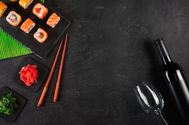 Sushi set sashimi e sushi rolls, garrafa de vinho e um copo servido na ardósia de pedra Foto Premium