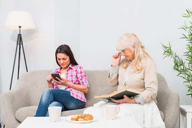 Suspeito mãe espiando sua filha adulta procurando mensagens em um smartphone Foto gratuita