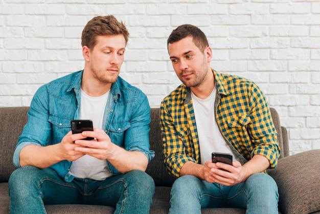Suspeitos dois amigos do sexo masculino sentado no sofá usando telefone celular Foto gratuita