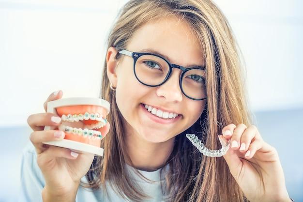Suspensórios invisíveis segurados por uma jovem sorridente Foto Premium