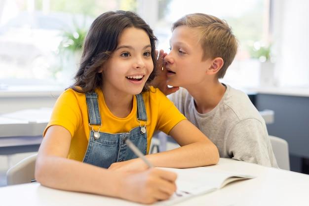 Sussurro de menino para menina na classe Foto gratuita