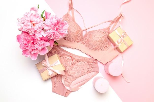 Sutiã de renda rosa elegante feminino e calcinha, flores velas cor de rosa, um buquê de peônias lindas, presentes Foto Premium