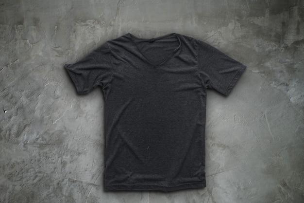T-shirt cinza no fundo da parede de concreto. Foto Premium