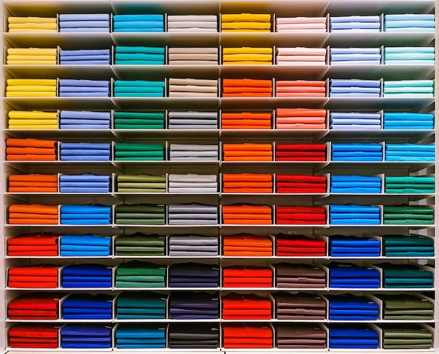 T-shirt de cor diferente são ordenadamente empilhados em uma fileira nas prateleiras da loja. Foto Premium
