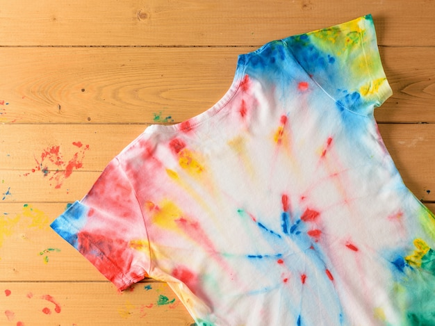 T-shirt pintada no estilo de tie dye em uma mesa de madeira Foto Premium