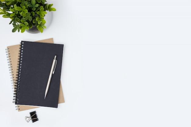 Tabela branca da mesa de escritório com cadernos, pena e planta. vista superior com copyspace, plana leigos. Foto Premium