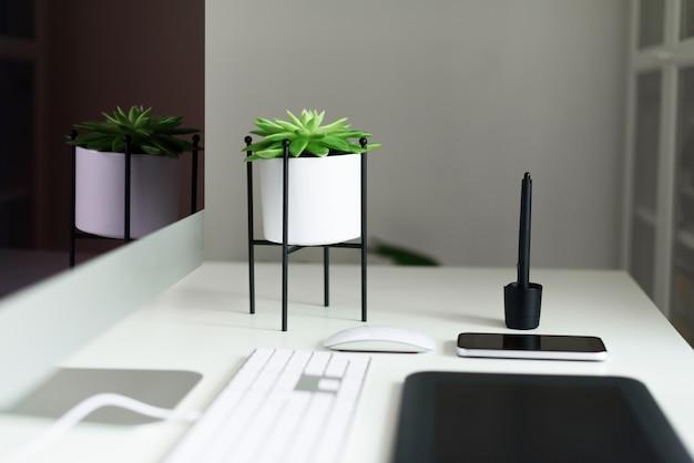 Tabela branca da mesa de escritório com teclado de computador, rato, monitor, tabuleta gráfica, smartphone, planta suculento e outros materiais de escritório. Foto Premium