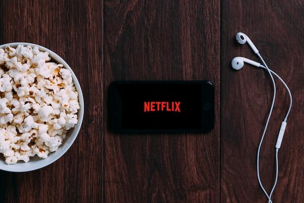 Tabela com garrafa de pipoca e logotipo netflix na apple iphone e fone de ouvido. Foto Premium