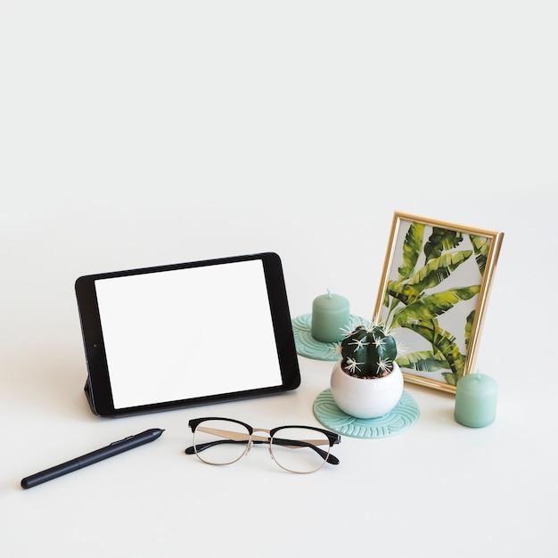 Tabela com tablet perto de moldura, caneta e óculos Foto gratuita