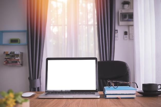 Tabela de madeira com a tela vazia no portátil, no papel do caderno e em um copo de café na sala de visitas. Foto Premium