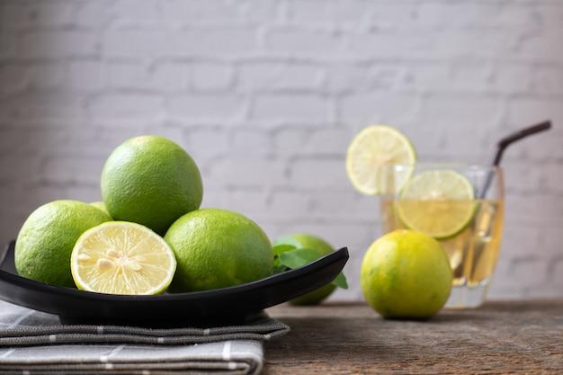Tabela de madeira com suco de limão recentemente espremido e limão cortado. Foto Premium