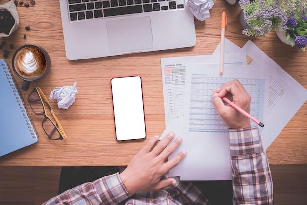 Tabela de madeira do escritório com o homem de negócios que verifica o papel do relatório, tela vazia no móbil, vista de cima da tabela. Foto Premium