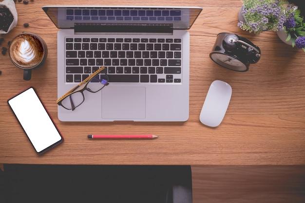 Tabela de madeira do escritório com portátil e documento, copo de café do latte. Foto Premium