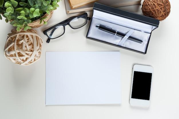 Tabela de mesa de escritório branco com um monte de coisas sobre ele. vista do topo Foto Premium