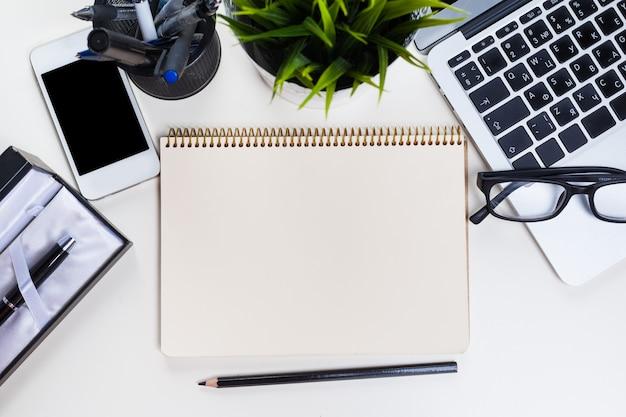 Tabela de mesa de escritório branco com um monte de coisas sobre ele. Foto Premium