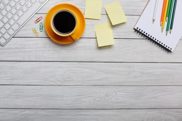 Tabela de mesa de escritório com computador, suprimentos, xícara de café e flor. isolado Foto Premium