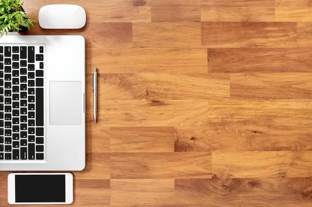 Tabela de mesa de escritório de madeira com computador portátil, smartphone e suprimentos. vista superior, fundo plano leigo com copyspace Foto Premium