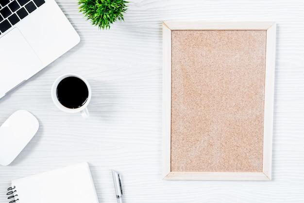 Tabela e equipamento de madeira brancos da mesa de escritório para trabalhar com café e placa vazia na vista superior e no conceito liso do raio. Foto Premium
