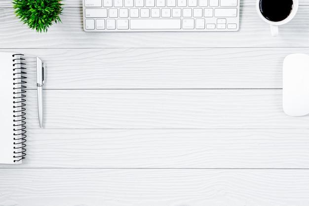 Tabela e equipamento de madeira brancos da mesa de escritório para trabalhar com café na vista superior e no conceito liso do raio. Foto Premium