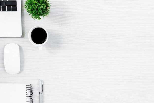 Tabela e equipamento de madeira brancos da mesa de escritório para trabalhar com café preto na vista superior e no conceito liso do raio. Foto Premium
