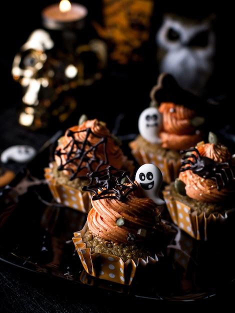 Tabela extravagante do partido do alimento de halloween com o queque e os bolinhos do queque da abóbora. Foto Premium