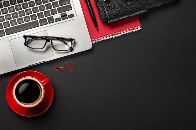 Tabela preta da mesa de escritório com o laptop da tela vazia, o caderno, o rato, a xícara de café e o outro escritório. Foto Premium