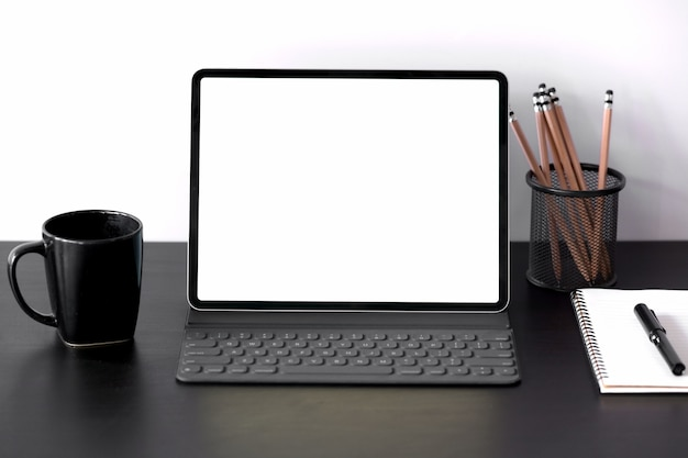 Tablet com caixa de teclado inteligente com tela em branco na mesa de madeira escura Foto Premium