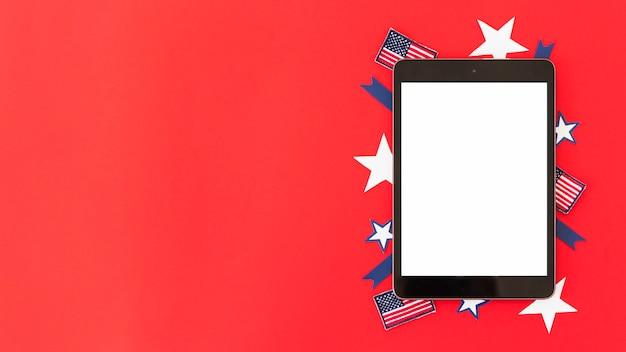 Tablet com elementos decorativos da bandeira americana na superfície vermelha Foto gratuita