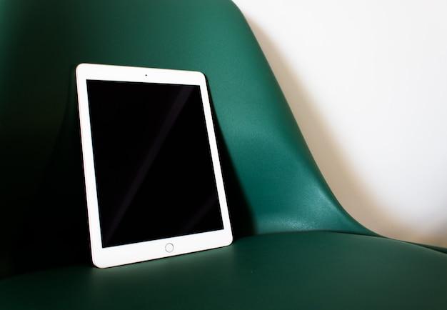 Tablet com tela em branco em uma cadeira Foto gratuita