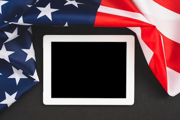 Tablet com tela vazia na fronteira com a bandeira americana Foto gratuita