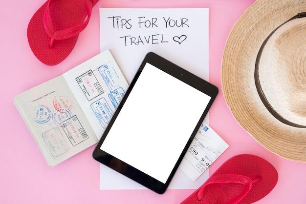 Tablet de vista superior rodeado por elementos de viagem Foto gratuita