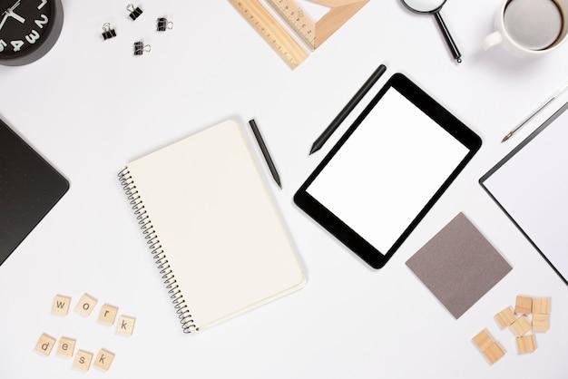 Tablet digital com caneta e material de escritório em fundo branco Foto gratuita