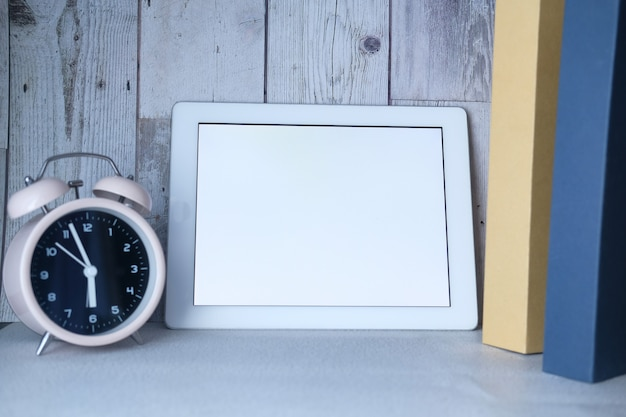 Tablet digital com tela vazia, relógio e pilha de livros na mesa Foto Premium