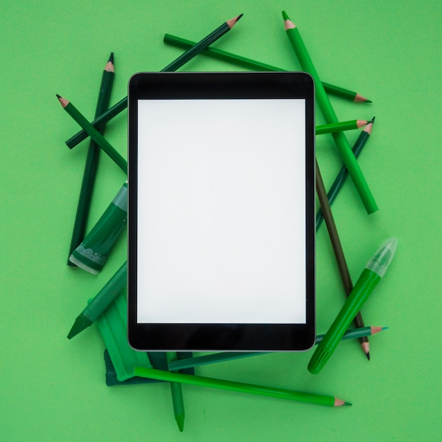 Tablet digital de close-up com tela em branco sobre lápis de cor; argila; tubo e marcador em fundo verde escuro Foto gratuita