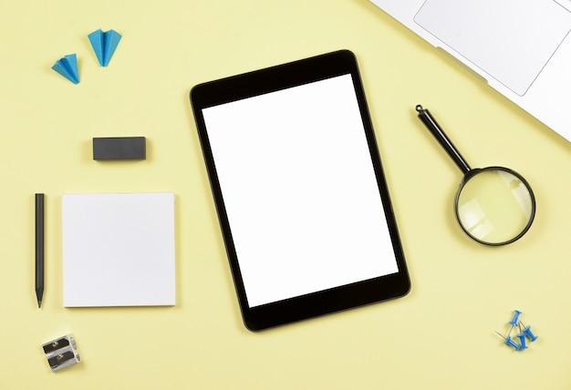 Tablet digital de tela em branco com material de escritório em pano de fundo amarelo Foto gratuita