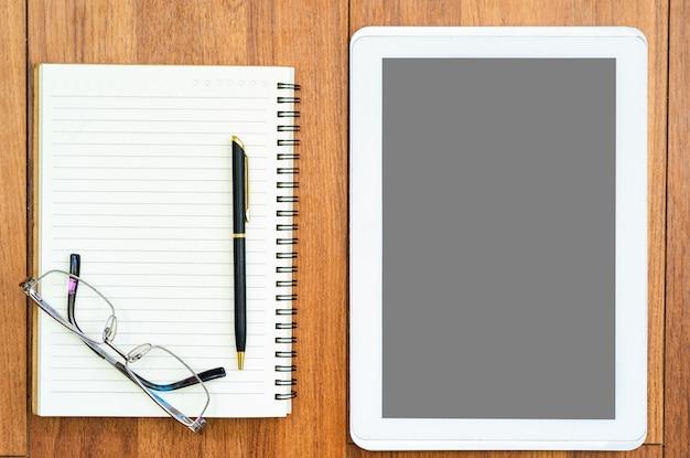Tablet digital e bloco de notas no deck de madeira Foto Premium