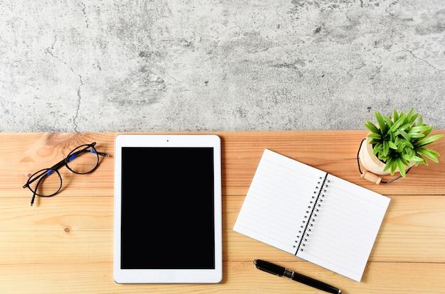Tablet em branco com computador portátil, óculos e cactos na mesa de madeira Foto Premium