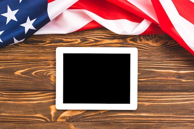 Tablet em fundo de madeira com bandeira dos eua Foto gratuita